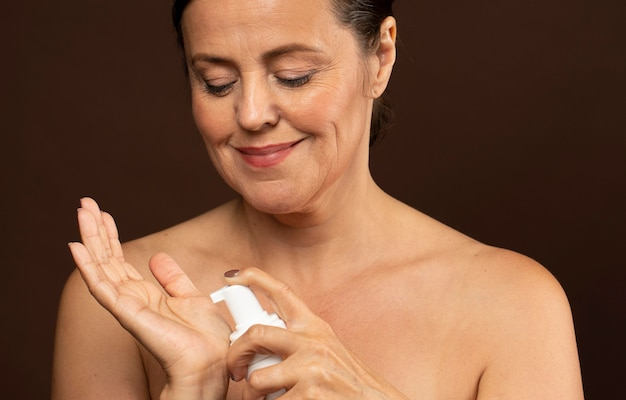 Smiley mature woman using cleanser for her face