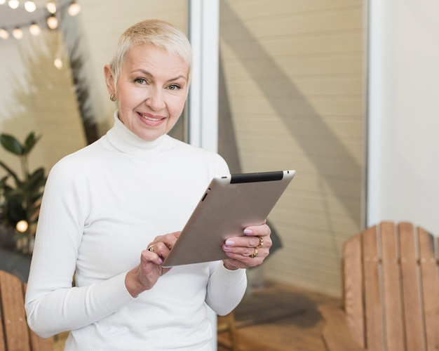 Smiley mature woman using her tablet