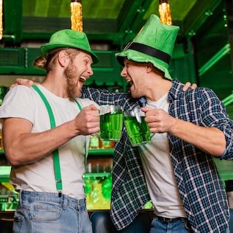 Uomini di smiley che celebrano st. patrick's day al bar con bevande