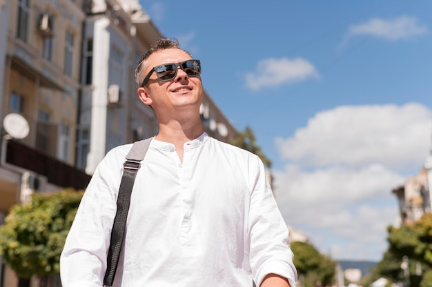 Smiley modern man walking in the city