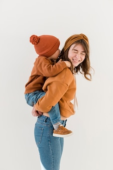 Smiley mom with son on piggy back ride