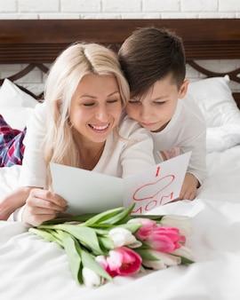 Улыбающаяся мама и сын читают поздравительную открытку