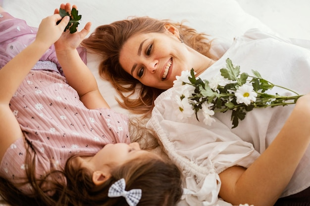 Smiley mother and daughter with bouquet of delicate spring flowers