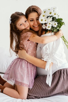 Smiley mother and daughter with bouquet of spring flowers