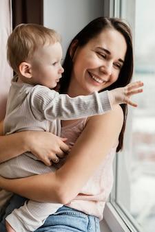 窓の近くに子供を抱いたスマイリーの母親