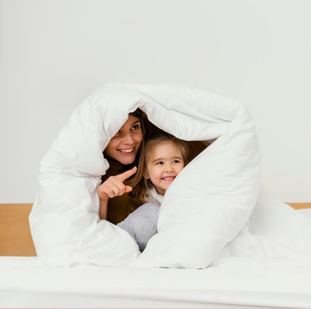 Smiley mother and kid hiding under blanket