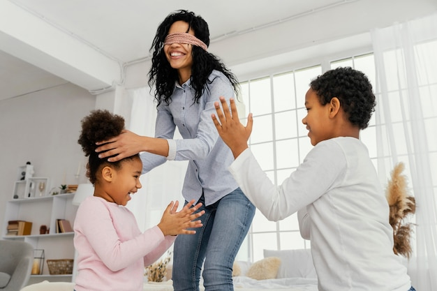Smiley mother playing with her children at home while blindfolded