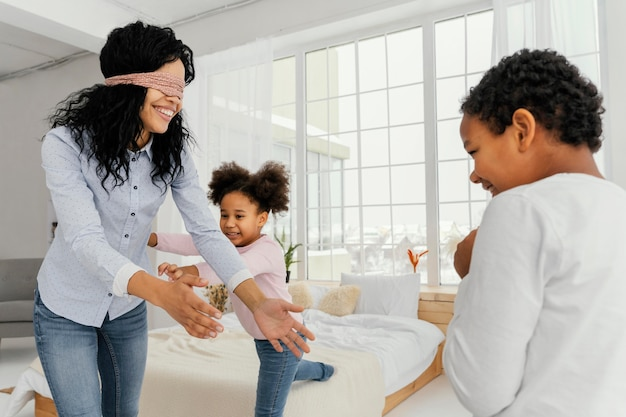 Madre di smiley che gioca con i suoi figli a casa