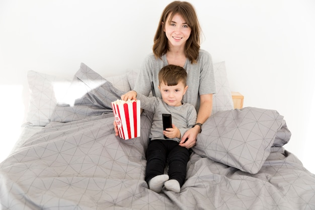 Smiley mother and son sharing popcorn