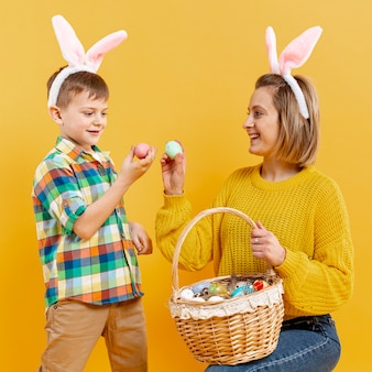 Smiley mother and son with painted eggs
