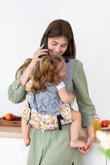 Smiley mother with phone holding girl