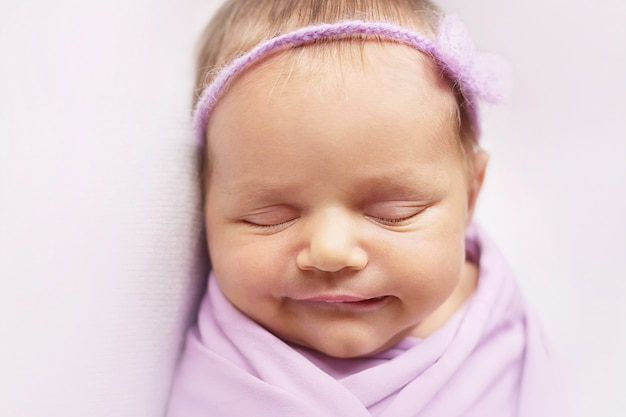 Smiley newborn baby girl is sleeping on the light pink background close-up
