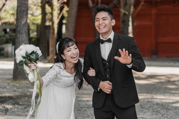 웃는 신혼 부부가 결혼 날을 흔들며 즐겁게
