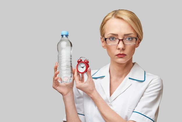 Смайлик медсестра или врач, держащий маленький красный будильник и бутылку воды, стоящую над серой стеной
