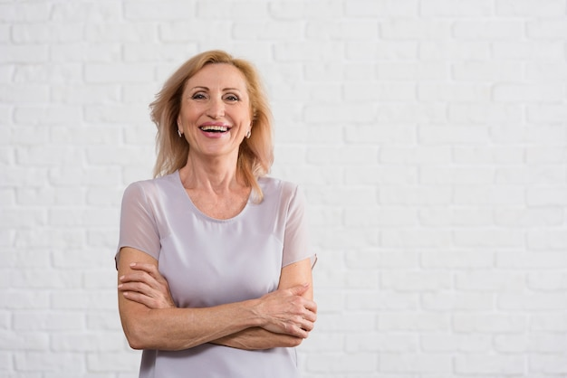 Smiley old lady looking at camera with brick background