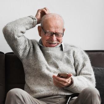 Uomo anziano di smiley in una casa di cura utilizzando smartphone