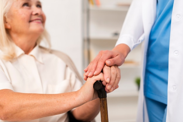 Smiley old woman holding hands with nurse close-up