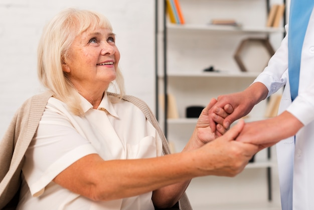 Smiley old woman holding hands with nurse