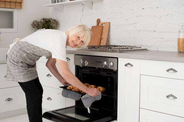 오븐에서 크로와상을 들고 웃는 늙은 여자