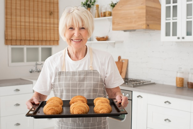Smiley old woman holding tray with croissants