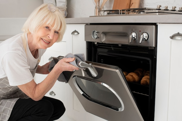 Smiley old woman opening the door of the oven