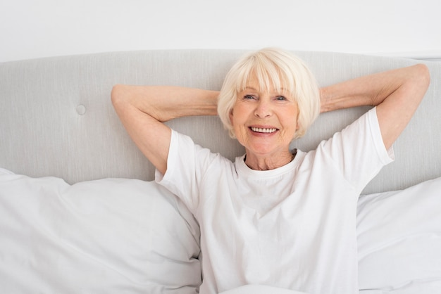 Smiley old woman sitting in the bedroom
