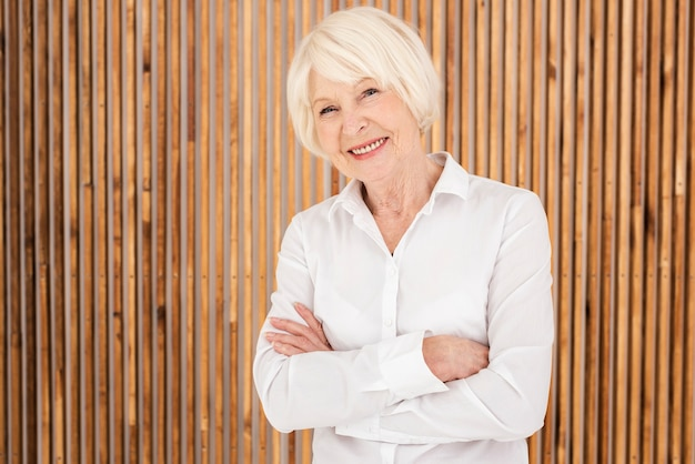 Smiley old woman standing next to a wooden wall