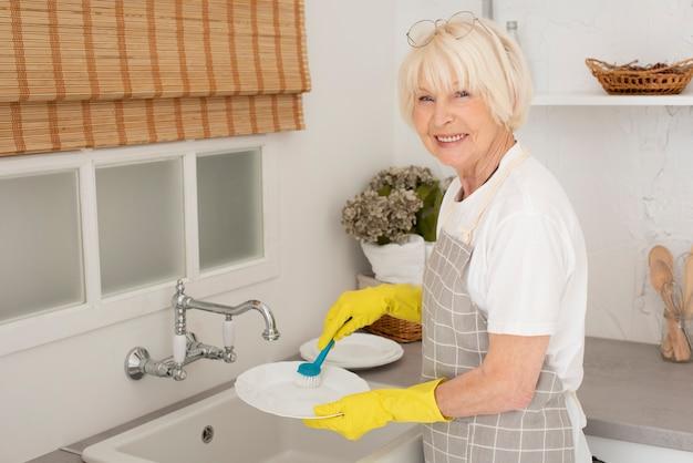 Улыбающаяся пожилая женщина моет посуду