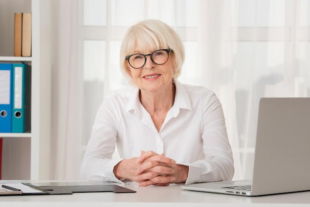 Smiley old woman with eyeglasses sitting in her office