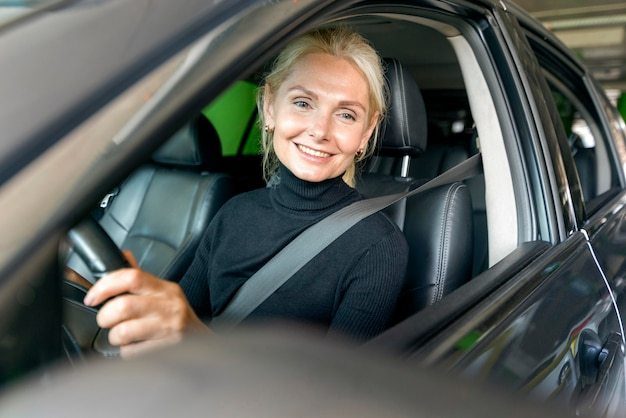 Smiley older business woman driving car