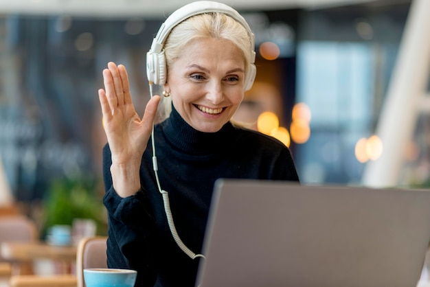 Смайлик пожилая деловая женщина, имеющая видеозвонок на ноутбуке с наушниками