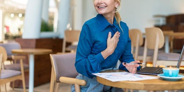 Смайлик пожилой деловой женщины, работающей на ноутбуке