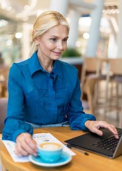 Donna più anziana di affari di smiley che lavora al computer portatile e che mangia caffè