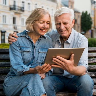 Smiley older couple looking at something on tablet Free Photo