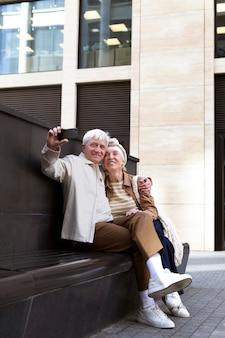 Улыбающаяся пожилая пара на открытом воздухе, делающая селфи вместе со смартфоном