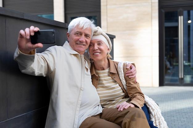 Faccina coppia di anziani all'aperto che si fa un selfie insieme allo smartphone