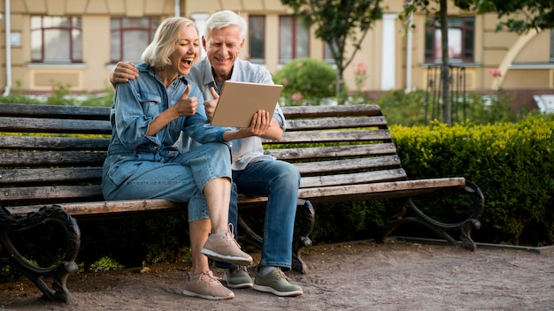 Smiley older couple outdoors with tablet