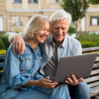 Smiley older couple sitting on bench outdoors with laptop