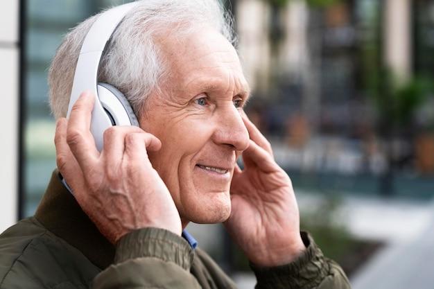 Uomo anziano sorridente in città che ascolta musica con le cuffie