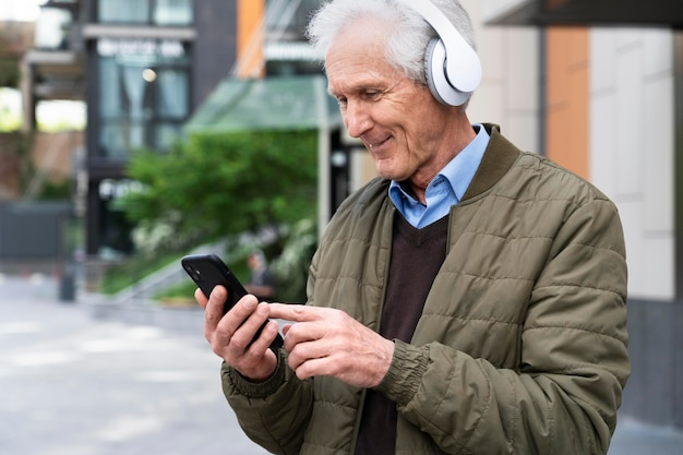 Smiley older man in the city listening to music on headphones