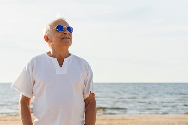 Smiley older man with sunglasses enjoying his time at the beach