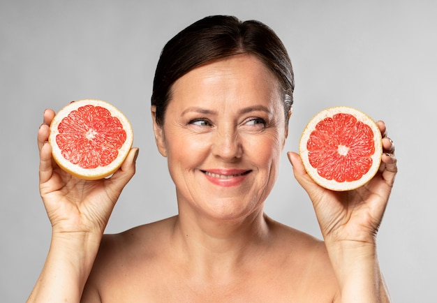 Smiley older woman holding half of grapefruit in each hand