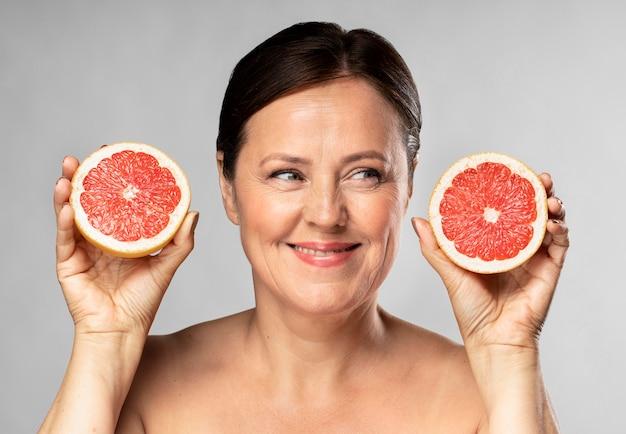 Donna più anziana di smiley che tiene metà del pompelmo in ogni mano