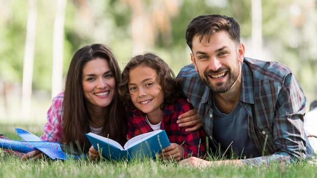 Улыбающиеся родители и ребенок читают вместе