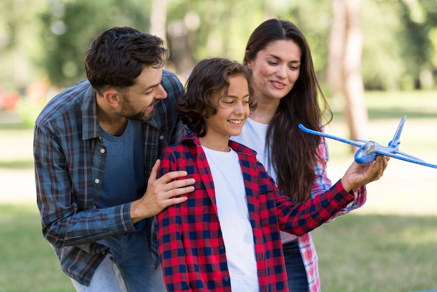 Smiley parents and child playing with airplane together outdoors