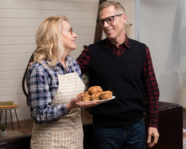 Smiley parents holding plate with muffins