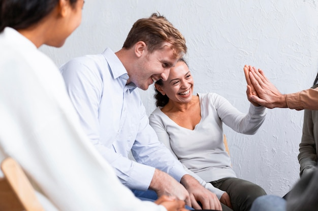 Smiley people at a group therapy session high-fiving each other