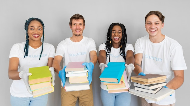 Smiley people holding a bunch of books to donate them