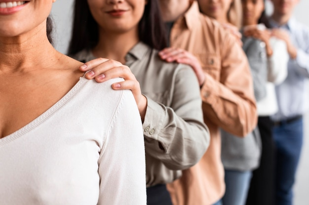 Smiley people touching shoulders at a group therapy session