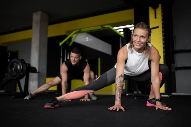 체육관 전체 샷에서 훈련하는 웃는 사람들